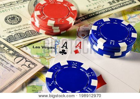 Las Vegas on map with money, poker chips and pair of aces playing cards. Horizontal image.