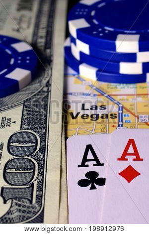 Las Vegas on map with money, poker chips and pair of aces playing cards. Vertical image.