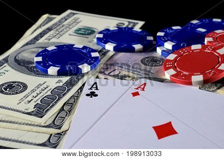 Playing cards, poker chips and money on black background.
