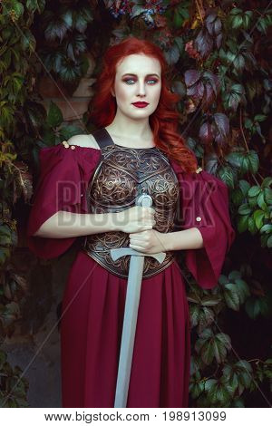 Beautiful red-haired woman with a sword in her hands.