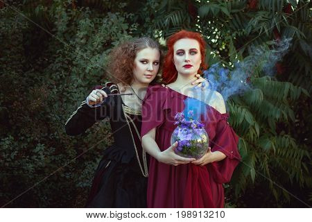 Two women are engaged in witchcraft they are shamans and make spells.