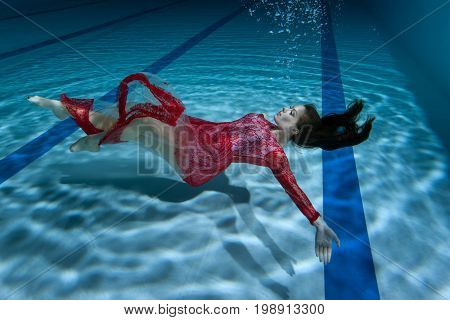 Dress of the woman flutters under the water she dives underwater.