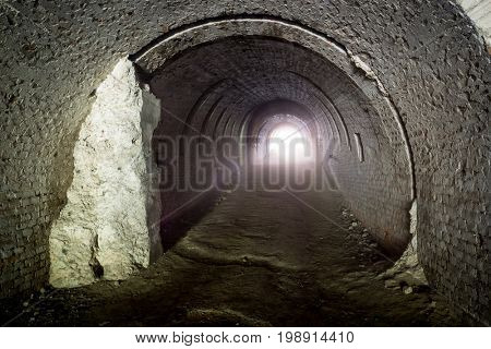 Old lost underground tunnel with light in end