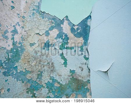 Cracked texture of the paint. Old paint on the wall with old plaster and several layers of paint surface close-up. Macro photography colored texture of background