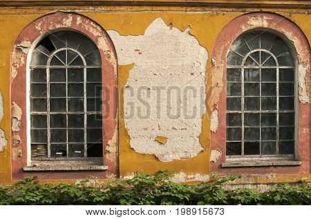 Old vintage weathered crumbling grunge glass windows of abandoned industrial building