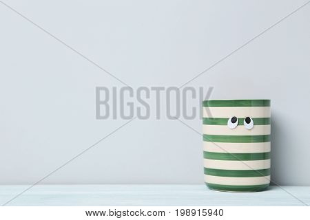 Striped Cup With Googly Eyes On A Grey Background