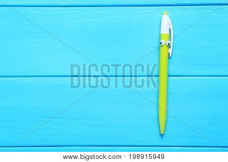 Pen With Googly Eyes On Blue Wooden Table