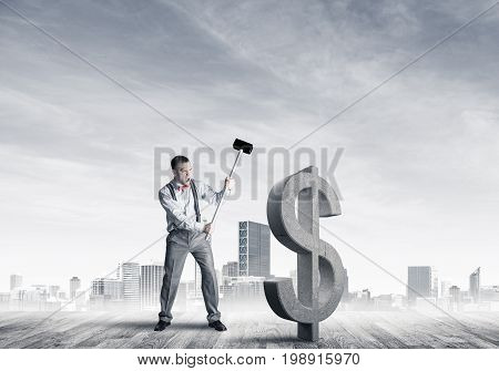 Young furious businessman going to crash with hammer stone dollar symbol