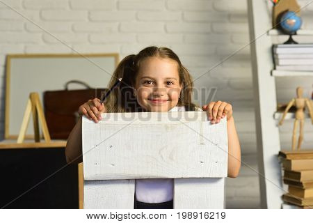 Schoolgirl Sits On White Chair, On Defocused Study Room Background