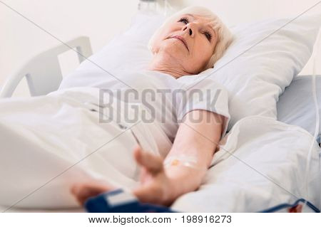 Keep it in check. Delicate vulnerable aged woman lying in bed in hospital and undergoing usual treatment while recovering from disease