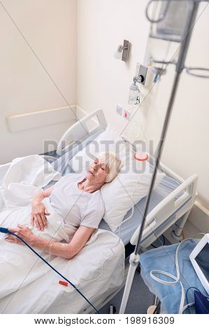 Medical service. Ailing tired aged lady resting while receiving needed medication through drip and recovering from a disease