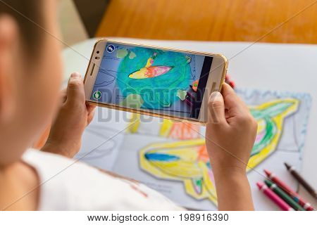 ZhongshanChina-August 8 2017:kid playing Augmented Reality popup paintings of a filled dolphin via mobile. AR and VR games become more and more popular.
