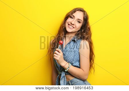 Portrait Of Young Woman With Lollipop On Yellow Background