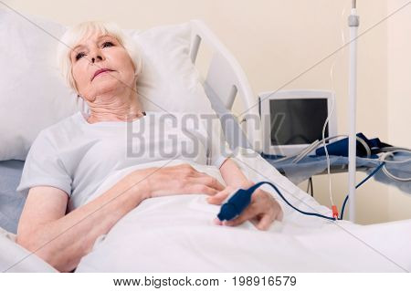Many devices. Vulnerable sore senior lady resting on bed and restoring her strength while recovering from heart stroke