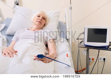 Following doctors orders. Senior pretty sock lady lying in hospital bed and getting medication through a drip while recovering from disease