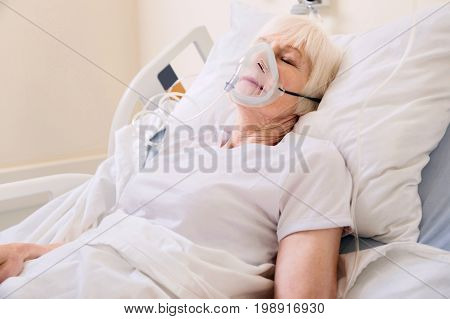 Take a deep breath. Unstable feeble aged lady lying in hospital bed and sleeping while recovering from serious disease