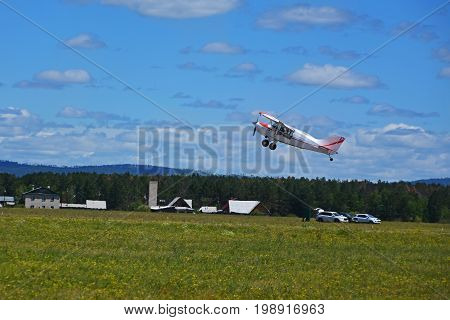Small plane takes off from grassy field airstrip