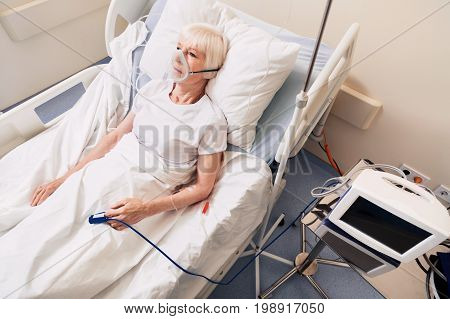 Vital devices. Worried ailing senior woman lying on hospital bed while doctors using life supporting system for ensuring recovery