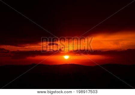 Orange sunset with sun and soft light rays visible through dark cloud cover