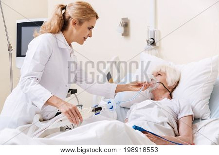 We will use some devices. Wise young energetic woman treating her patient and making her wearing oxygen mask for ensuring her proper breathing