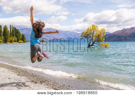 New Zealand travel happy tourist woman jumping of joy at Wanaka lake landscape with lone tree, famous attraction.