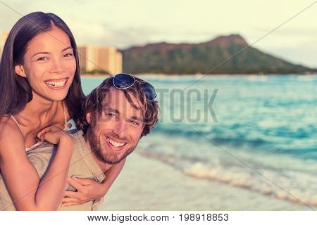 Happy interracial couple, woman piggybacking on man on Waikiki beach with Diamond Head Mountain landscape. Healthy people portrait, Honolulu, Hawaii. Travel holidays destination.