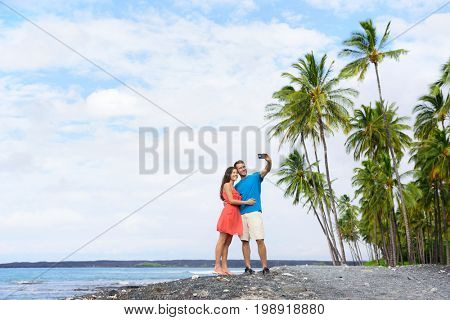 Selfie couple on Hawaii beach vacation with palm trees and volcanic black sand in Big island of Hawaii, USA. Hawaiian holidays getaway. Happy people on summer holidays.