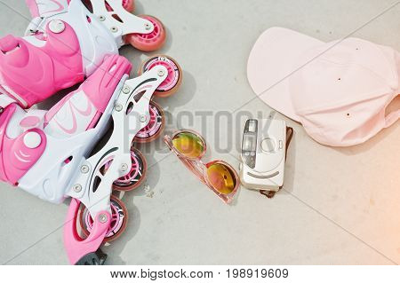Close-up Photo Of Pink Rollerblades Laying Along With An Antique Camera, Sunglasses And A Pink Cap.