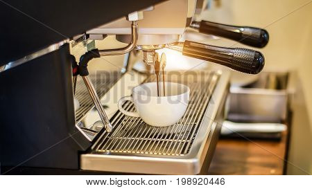 Coffee flowing into a cup from espresso machine