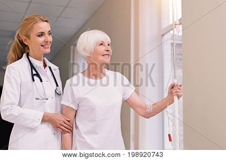 Pretty window view. Neat prominent wise woman looking after elderly lady and allowing her taking a walk while assisting her with that