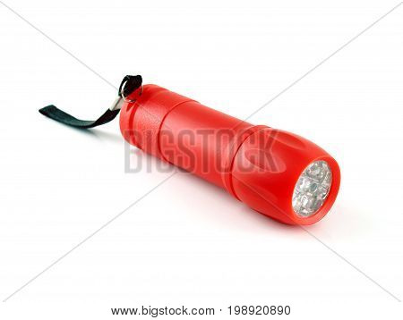 close up red plastic flashlight with LED light and black strap isolated on white background