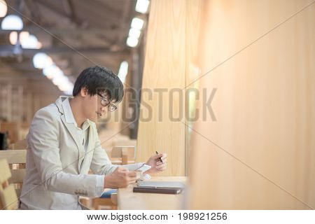 Young Asian casual business man using smartphone and checking his work at vintage cafe smart urban lifestyle with digital device and technology gadget trends work life balance concepts