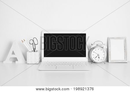 Workplace with white laptop on table education or business concept