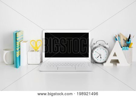 Workplace with laptop on white table business or education concept