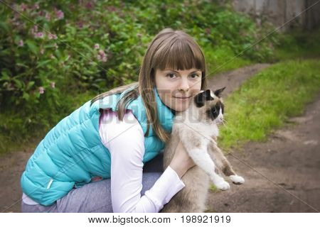 Girl with cat in her arms. Young woman and cat. Girl with a cat in the village. Portrait of a girl with a cat. The love of a pets. Beautiful Russian girl with cat