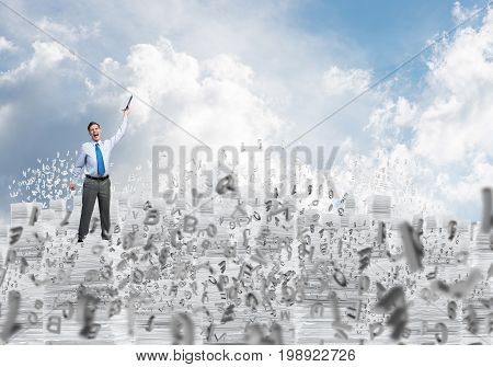 Businessman keeping hand with book up while standing among flying letters with cloudly skyscape on background. Mixed media.