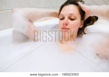 young beautiful brunette woman takes bubble bath.
