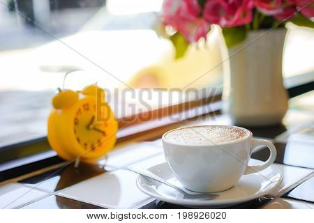 Capuccino coffee and Yellow clock on White and Black Table in Cafe
