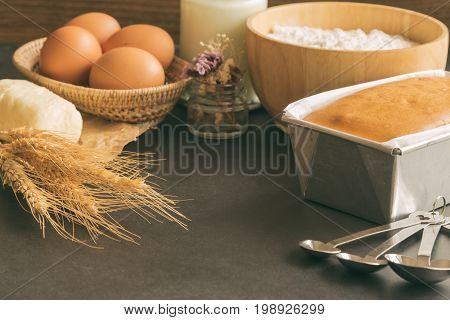 Bakery background with butter cake and ingredients: eggs milk flour and butter. Loaf of butter cake or pound cake on granite table with copy space. Homemade delicious pound cake in warm tone for background or wallpaper.