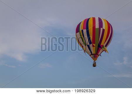 Multi-colored hot air balloon floats through the sky at dusk at Warren County Farmer's Fair on 8/1/17