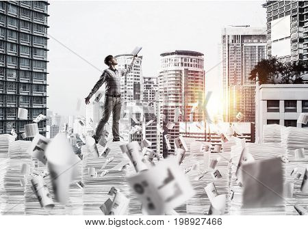 Side view of man in casual wear keeping hand with book up while standing among flying papers with cityscape and sunlight on background. Mixed media.