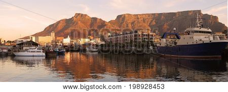 FROM CAPE TOWN, SOUTH AFRICA, THE SUN STARTING TO SET OVER THE VITORIA AND ALFRED WATERFRONT