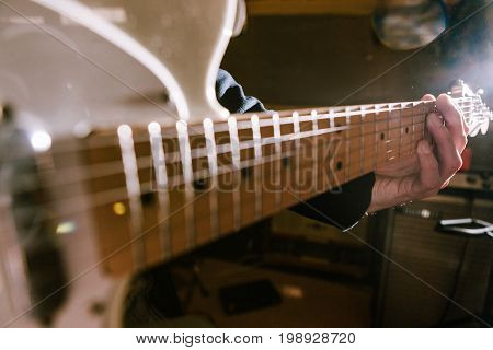 Electric guitar riff in guitarist hands in selective focus. Music recording process, unrecognizable performer. String instrument background