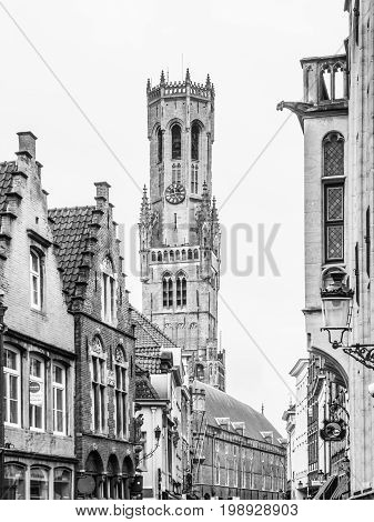 The Belfry Tower, aka Belfort, of Bruges, medieval bell tower in the historical centre of Bruges, Belgium. Close-up view of the top. Black and white image.