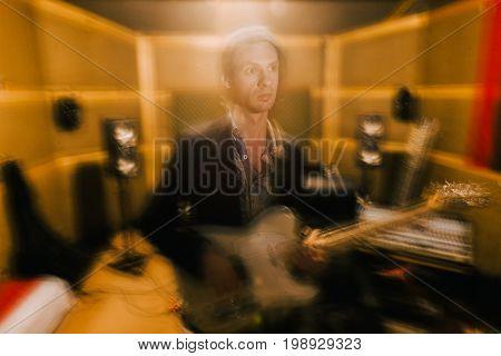 Guitarist creative portrait in recording studio. Blurred effect, musical album process, grunge music repetition