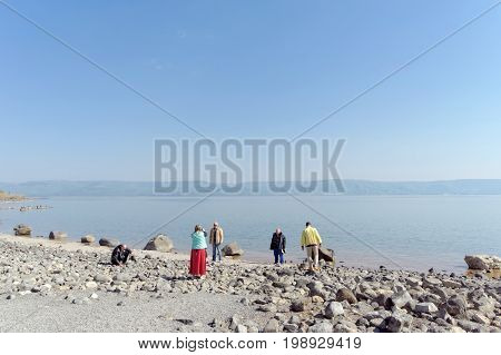 Israel. - February 17.2017. Pilgrims are photographed on the shore of the Sea of Galilee.