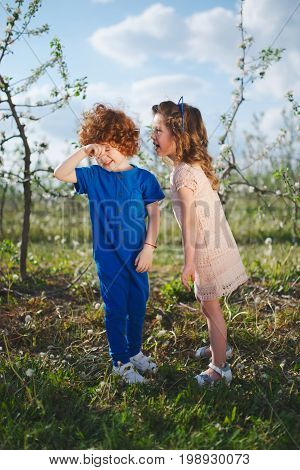 happy little boy and girl in blooming garden
