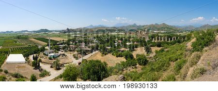 Ancient ruins of Aspendos. In the background the aqueduct. Panorama. Turkey.
