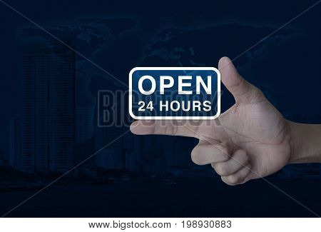 Open 24 hours icon on finger over world map and modern city tower Business full time service concept Elements of this image furnished by NASA
