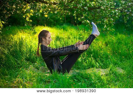 Woman Doing Yoga Outdoors On Green Grass